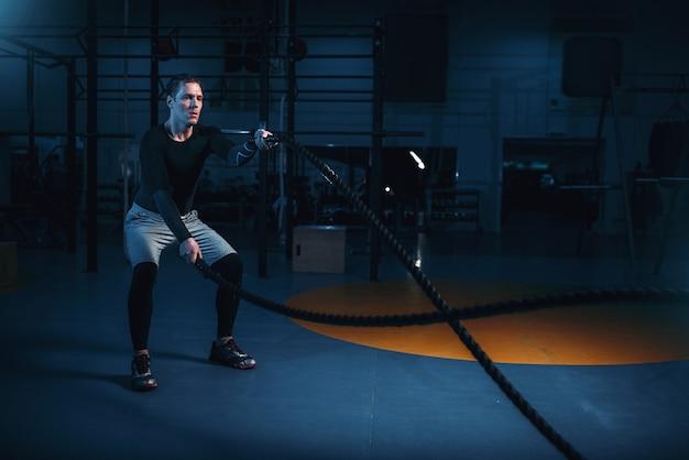 Esportista em treinamento, treino com cordas de batalha no ginásio.