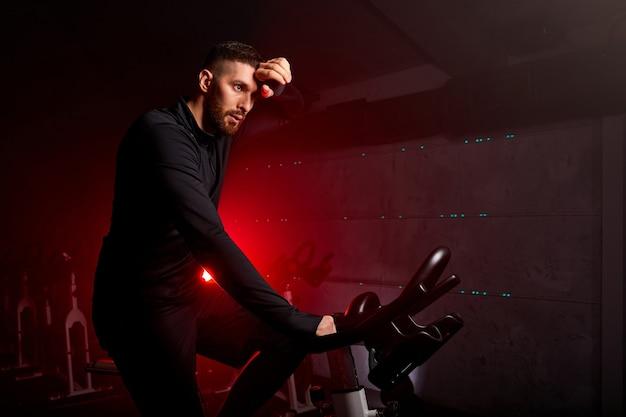 Esportista enxuga o suor do rosto, exausto de treinar de bicicleta na academia, precisa de descanso, com roupas esportivas