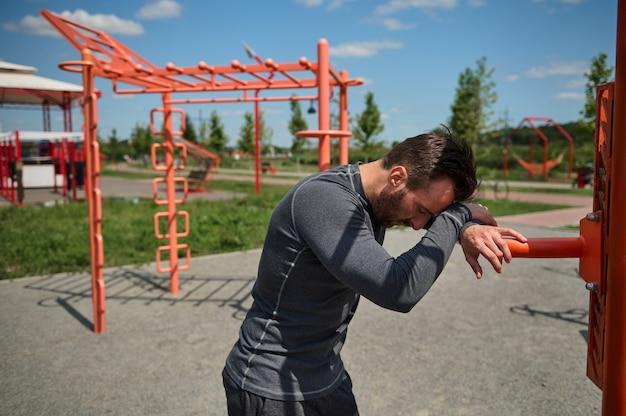 Esportista europeu caucasiano exausto, apoiando a testa em uma barra transversal, descansando após um treino intenso ao ar livre em um campo de esportes de verão