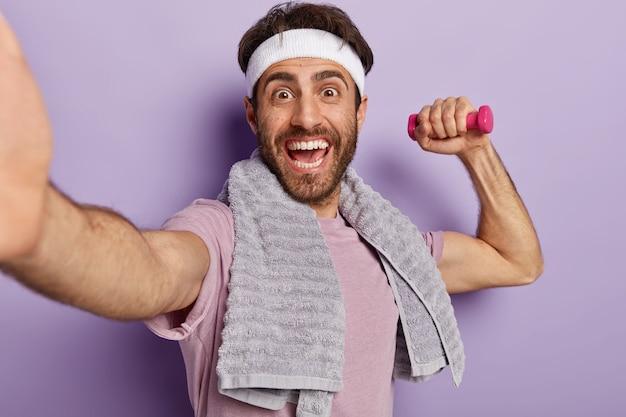 Esportista europeu enérgico ri com alegria, trabalha no bíceps com halteres, faz uma selfie, tem uma toalha no pescoço, usa uma faixa na cabeça