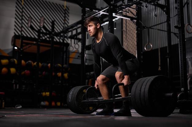 Esportista, exercitando-se com barra. jovem fisiculturista masculino e musculoso, caucasiano, fazendo exercícios de levantamento de peso no ginásio escuro, usando equipamento esportivo Foto Premium