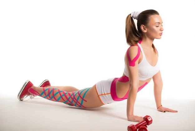 Esportista fazendo exercícios com adesivos no corpo