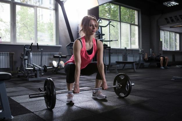 Esportista fazendo levantamento terra com barra pesada
