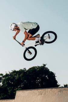 Esportista fazendo saltos extremos no skatepark vista de ângulo baixo