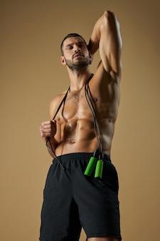 Esportista forte em roupas esportivas pretas em pé no estúdio