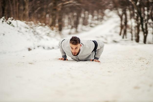 Esportista forte fazendo flexões na natureza no caminho de neve no inverno. estilo de vida saudável, fitness de inverno, exercícios de força