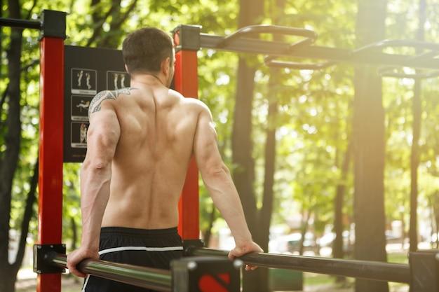 Esportista irreconhecível malhando em equipamentos de ginástica na floresta