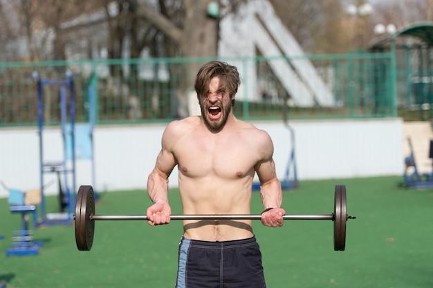 Esportista levanta a barra no estádio. homem com torso atlético, braços fortes. atleta grita treinamento com peso. levantamento de peso, musculação, fitness, esporte. potência, energia, conceito de força