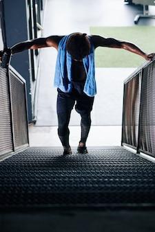 Esportista lutando subir as escadas após o dia da perna