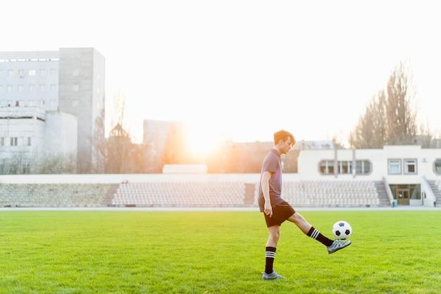 Esportista malabarismo bola de futebol