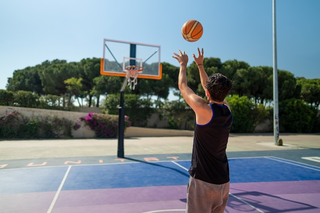 Esportista masculino jogando basquete e jogando a bola no playgroun
