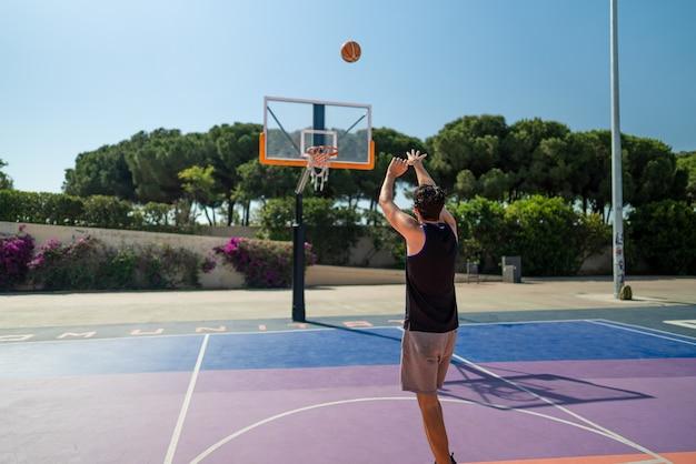 Esportista masculino jogando basquete, jogando a bola no playgroun