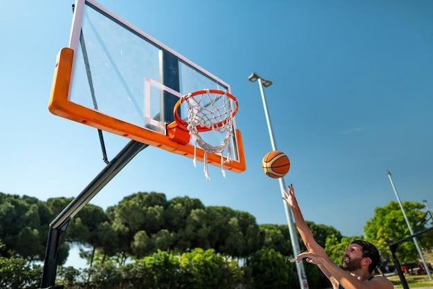 Esportista masculino jogando basquete jogando bola no playground