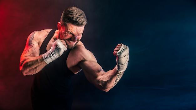 Esportista muay thai boxer lutando na parede preta com fumaça. conceito de esporte.