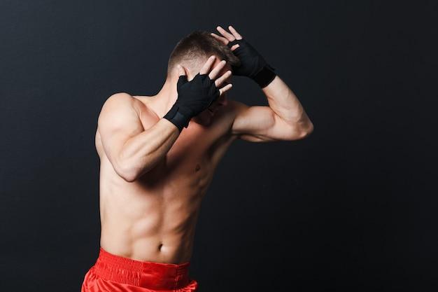 Esportista muay thai homem boxer posição anúncio cotovelo soco em fundo preto.