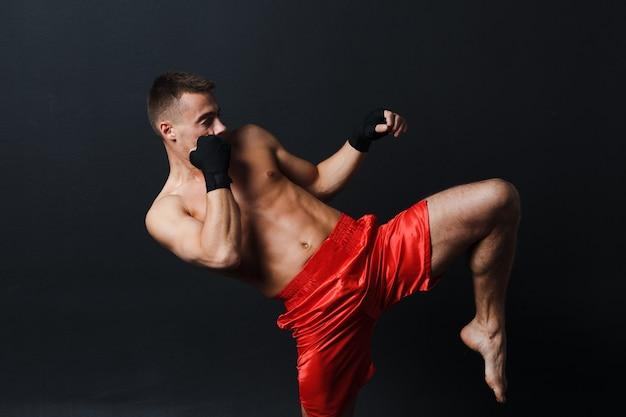Esportista muay thai homem boxer postura ad joelho chute em fundo preto.