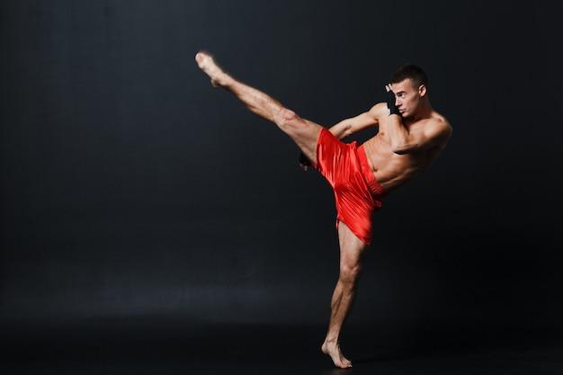 Esportista muay thai man boxer postura em fundo preto.