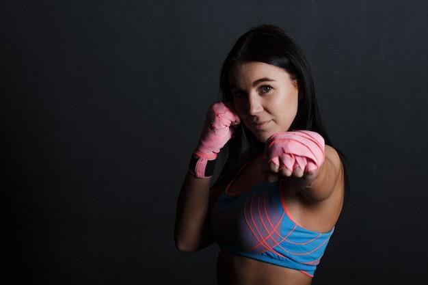 Esportista muay thai mulher boxer posando no estúdio de treinamento em fundo preto.
