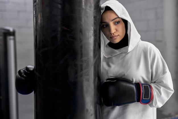 Esportista muçulmana cansada em pé perto de um saco de pancadas após um treino intenso, usando luvas de boxe e hijab branco esportivo, ela está olhando para o lado, exausta