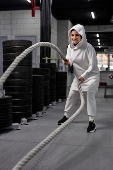 Esportista muçulmana em forma e tonificada, malhando em um ginásio de treinamento funcional, fazendo exercícios de cross fit com cordas de batalha, usando um hijab esportivo. motivação para treino cross fit