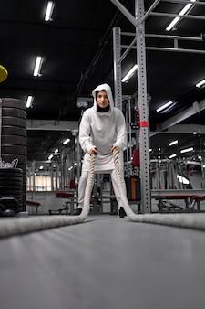 Esportista muçulmana em forma e tonificada, malhando no ginásio de treinamento funcional, fazendo exercícios crossfit com cordas de batalha, usando um hijab esportivo. motivação de treino cross-fit