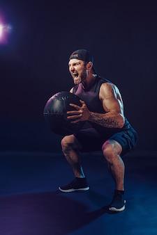 Esportista musculoso barbudo agressivo está malhando com uma bola de medicina isolada na parede escura.