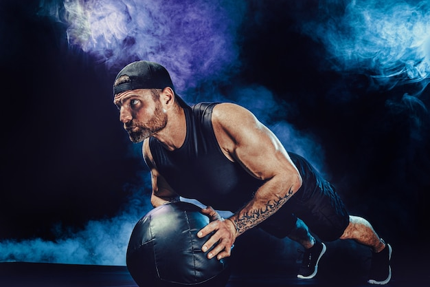 Esportista musculoso barbudo agressivo está malhando, empurre com uma bola de medicina isolada na parede escura do estúdio com fumaça.