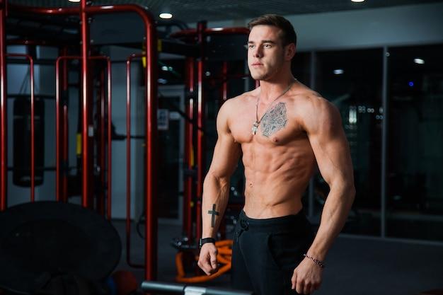 Esportista musculoso perfeito na academia com corpo em forma