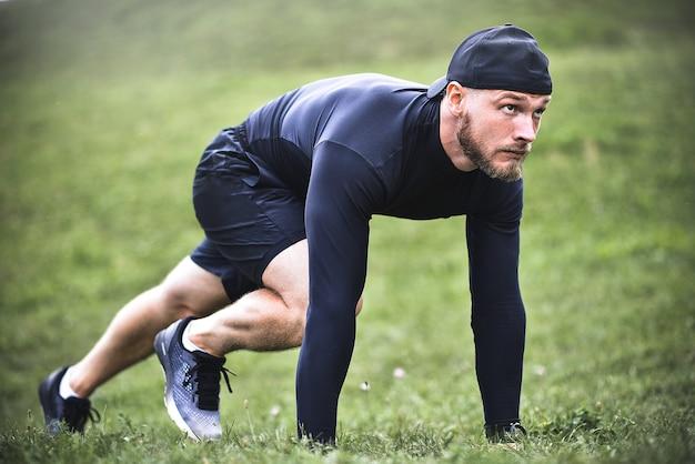 Esportista musculoso se alongando antes de um treino esportivo na rua no parque da cidade