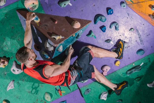 Esportista na parede de escalada