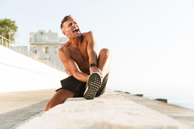 Esportista na praia tocando sua perna por causa de uma lesão dolorosa.