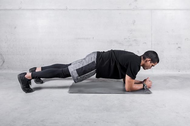 Esportista no abdômen de treinamento de postura de prancha