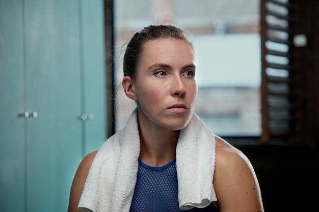 Esportista no vestiário com uma toalha no pescoço