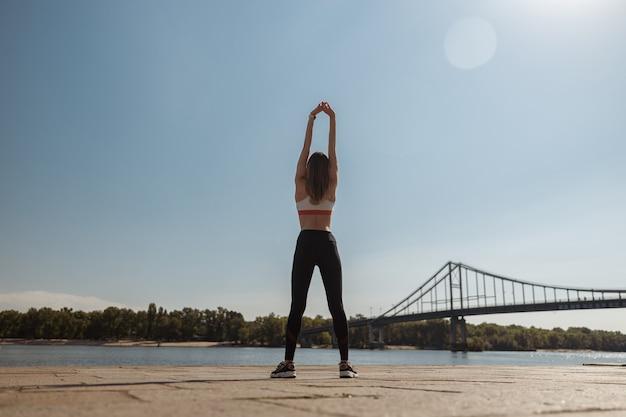 Esportista pratica exercícios esportivos em um dique da cidade moderna em um dia ensolarado