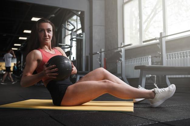 Esportista praticando exercícios abdominais com medicine ball, copie o espaço