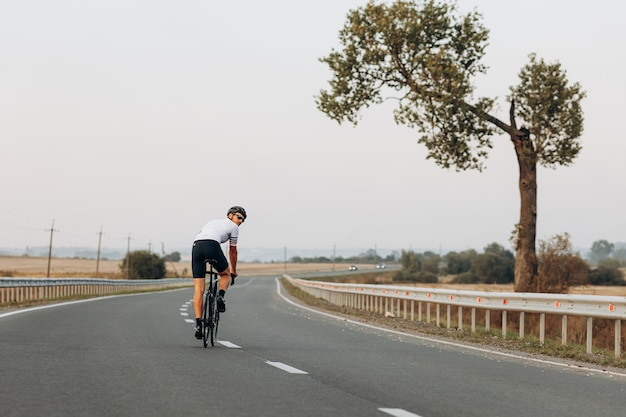 Esportista profissional vestido com roupa esportiva, praticando ciclismo durante o dia de verão ao ar livre