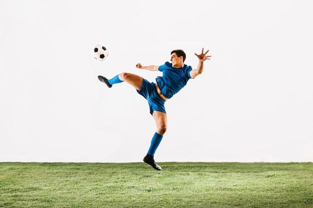 Esportista pulando e chutando a bola