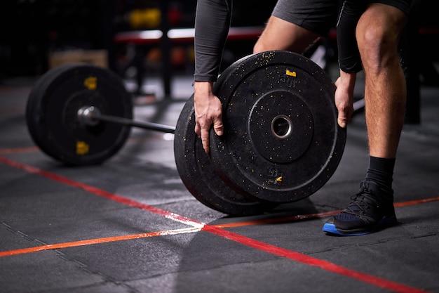 Esportista se preparando para o levantamento terra da barra durante a competição, passando um tempo no ginásio sozinho, trocando a barra pesada, conceito de treinamento cross fit. macho cortado