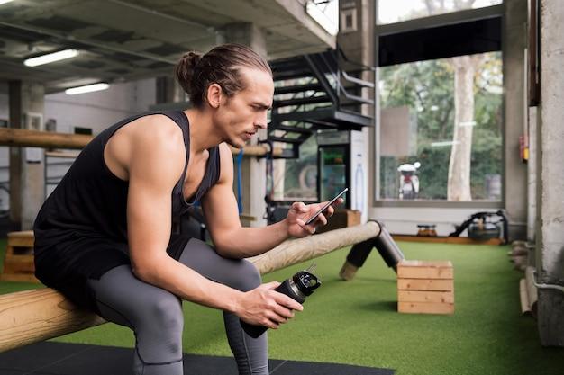 Esportista segurando uma garrafa consulta telefone na academia