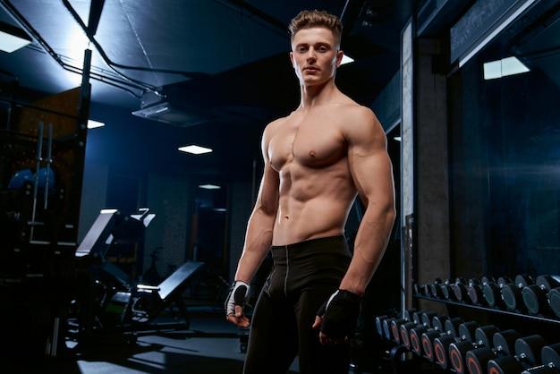 Esportista sem camisa posando no ginásio.