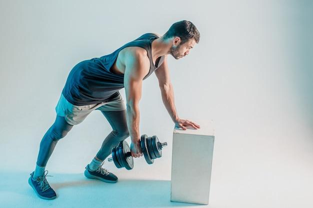 Esportista sério treinando músculos das costas com halteres. jovem barbudo homem europeu usa uniforme esportivo. isolado em fundo turquesa. sessão de estúdio. copie o espaço