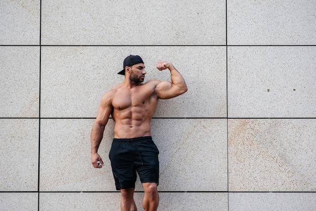 Esportista sexy fica de topless perto da parede. fitness, musculação