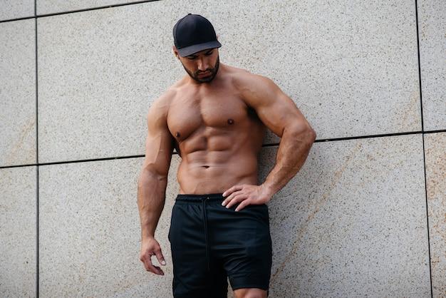 Esportista sexy fica de topless perto da parede. fitness, musculação.