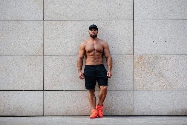 Esportista sexy fica de topless perto da parede. ginástica,