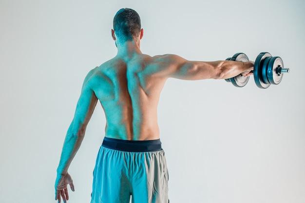 Esportista, treinamento de músculos do ombro com halteres. vista traseira do homem. isolado em fundo turquesa. sessão de estúdio. copie o espaço