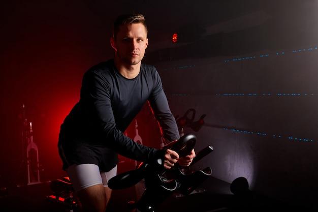 Esportista treinando em equipamento esportivo na academia, homem confiante e forte em agasalho tem treinamento intensivo em bicicleta no clube de fitness.