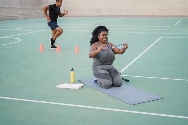 Esportistas fazendo rotina de exercícios ao ar livre no parque da cidade - concentre-se no rosto de uma mulher de tamanho grande