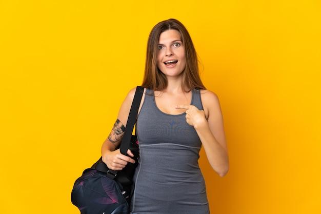 Esportiva eslovaca com bolsa esportiva isolada em fundo amarelo e expressão facial surpresa