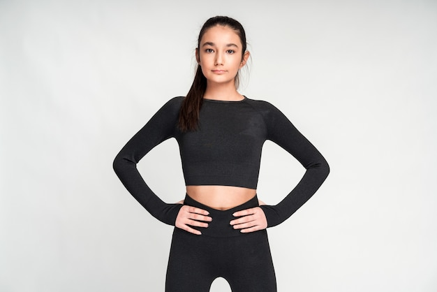 Esportiva jovem magro vestida com top preto recortado e calças posando contra o fundo da parede branca. menina asiática segurando as mãos na cintura e olhando para a câmera