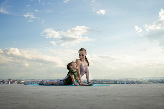 Esportiva mãe está fazendo exercícios com o filho. conceito de esportes.